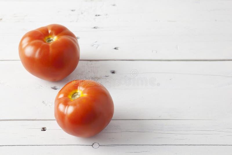 Zwei Tomaten auf einer weißen Tabelle lizenzfreie stockfotos