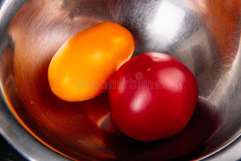 Zwei Tomaten in einer Eisensalatschüssel lizenzfreie stockfotos