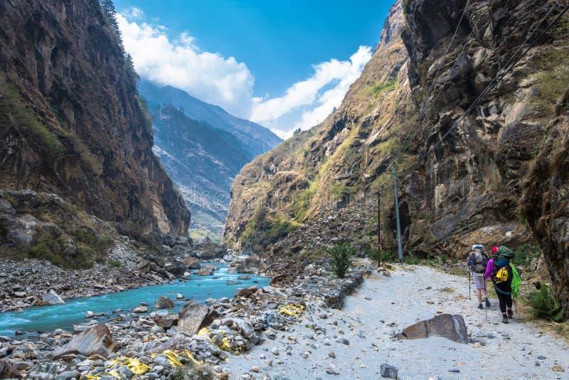 Zwei Touristen auf der Bank von einem Gebirgsfluss in Nepal stockbild