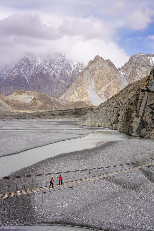 Zwei Touristen, die auf Hussaini-Hängebrücke acrsoss Hunza gehen stockfoto