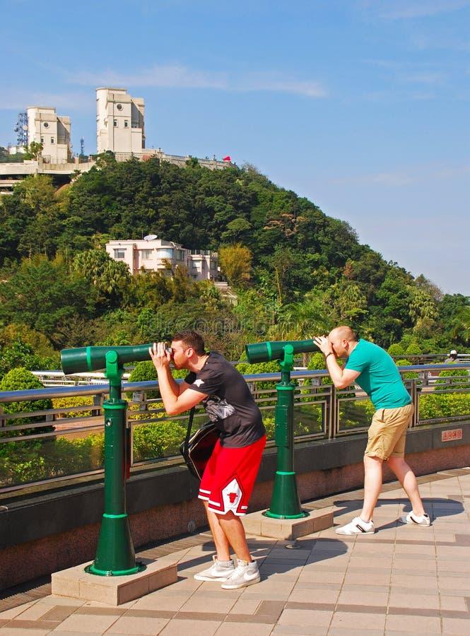 Zwei Touristen, die ein Paar des grünen touristischen panoramischen Teleskops an der Spitze, Hong Kong verwenden stockfotos