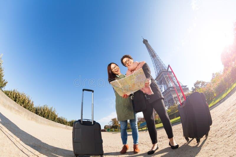 Zwei Touristen, die eine Karte von Paris am sonnigen Tag halten stockfotografie
