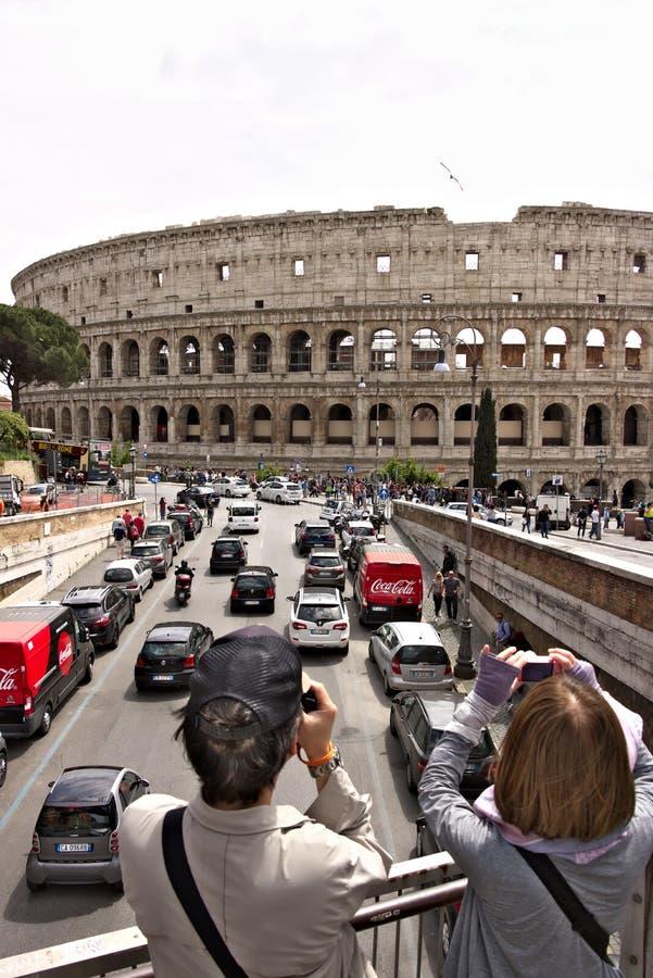 Zwei Touristen fotografieren das Colosseum Unten sehen Sie die Straße mit Autoverkehr und zwei roten Packwagen lizenzfreie stockfotografie