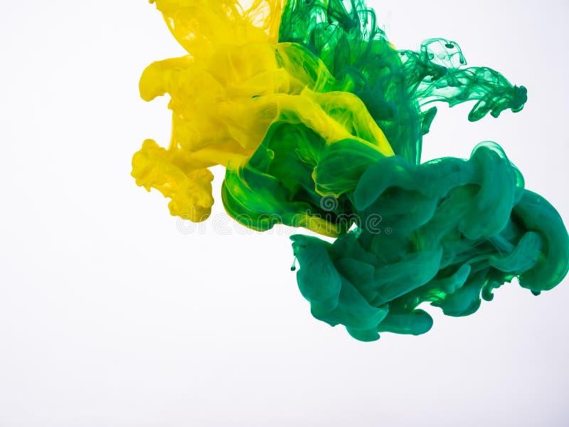 Zwei Tröpfchen der Acryltinte machen ein abstraktes Wirbeln unter Wasser Gelbe und grüne Tintenbewegung, fotografiert während her stockfotos