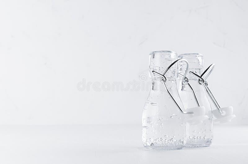 Zwei transparente Flaschen der Weinlese mit dem Funkeln sprudelt Mineralwasser, geöffneter Jochpfropfen auf weißem hölzernem Bret lizenzfreies stockbild