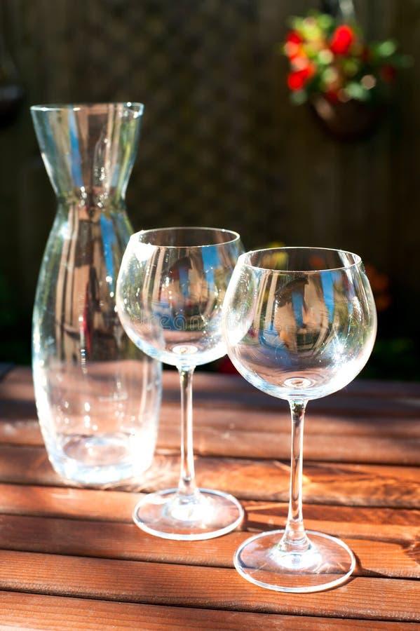 Zwei transparente glänzende leere Weingläser und Karaffe in den Strahlen von SU lizenzfreie stockfotos