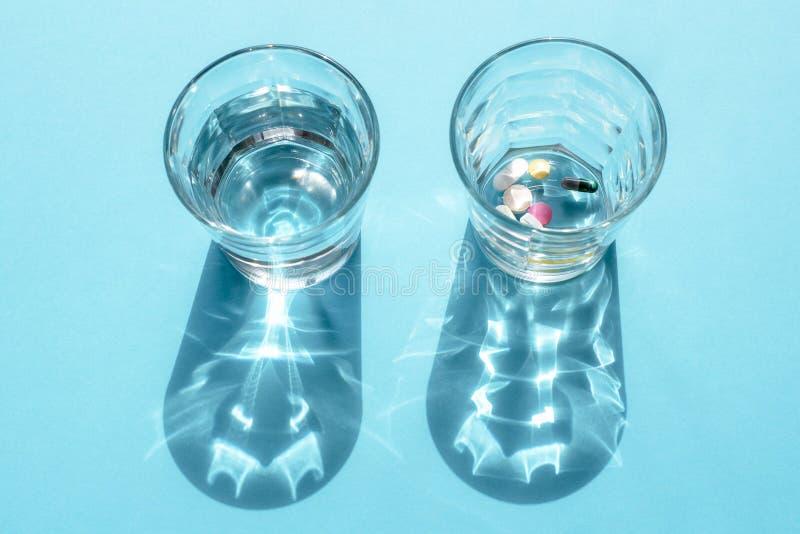 Zwei transparente Gläser In einem Wasser und in den anderen bunten Pillen lizenzfreie stockfotografie