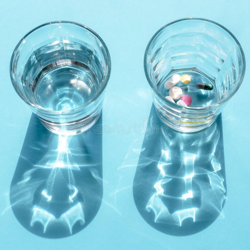 Zwei transparente Gläser In einem Wasser und in den anderen bunten Pillen stockbild