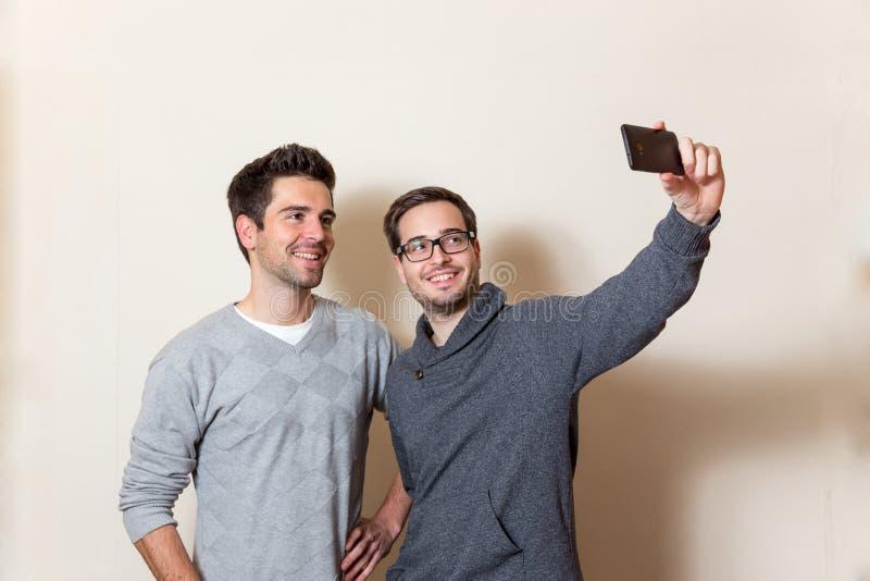 Zwei tun Sie Männer ein Selbstporträt mit einem Mobiltelefon lizenzfreie stockfotos