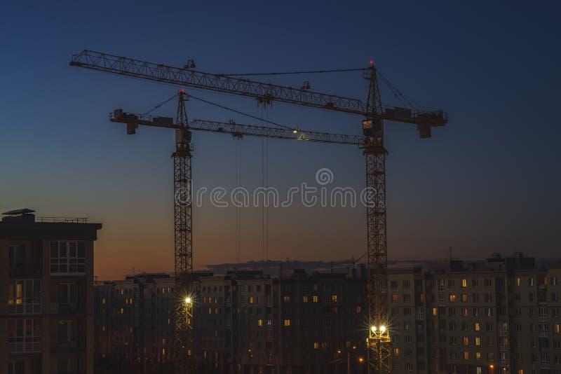 Zwei Turmkrane funktionieren spät nachts stockbild
