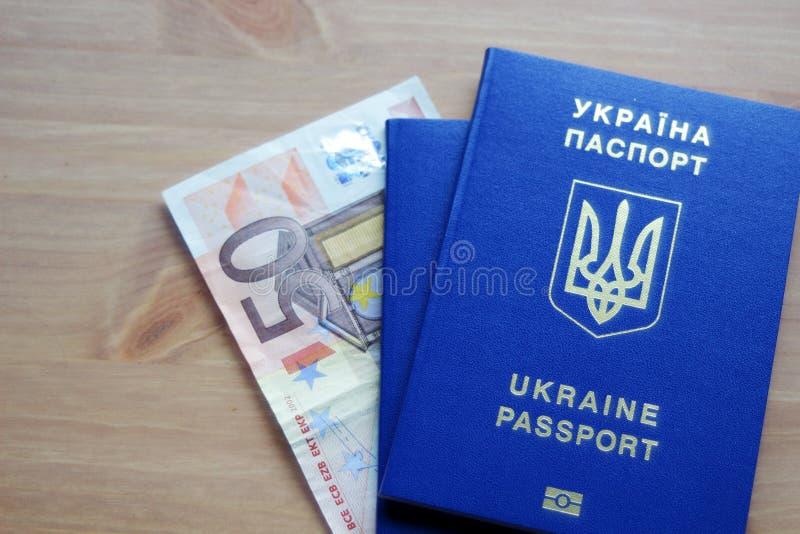 Zwei ukrainische biometrische Pässe mit der fünfzig-Euro-Banknote stockfotografie