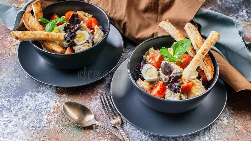 Zwei Umhüllungen Caesar-Salat mit Huhn, Wachtelei, Kirschtomaten, Croutons und Basilikum in den dunkelblauen Schüsseln auf einem  stockfoto