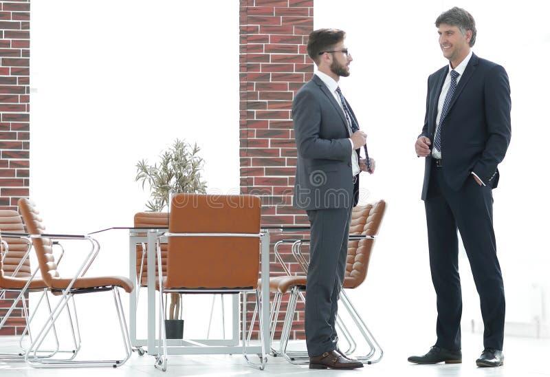 Zwei Unternehmensleiter, die über Geschäft im Büro sprechen lizenzfreie stockfotos