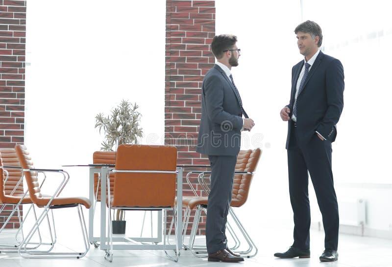 Zwei Unternehmensleiter, die über Geschäft im Büro sprechen lizenzfreie stockbilder