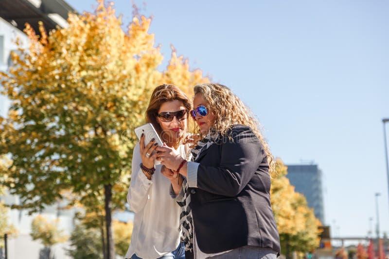 Zwei unternehmungslustige Frauen sind wiederholend und Stellung nehmend zu etwas, sehen sie auf einer Tablette stockfoto