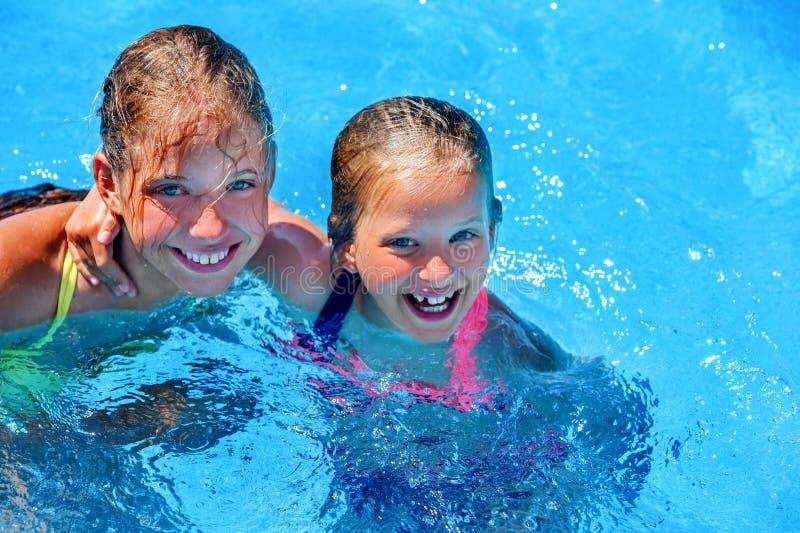 Zwei unterschiedliches Alterskinderschwimmen im Swimmingpool lizenzfreie stockbilder