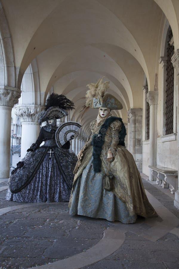 Zwei venetianische Karnevals-Zahlen in einem bunten Kostüm und in einer Maske unter dem Säulengang des Doge ` s Palastes Venedig  lizenzfreies stockbild