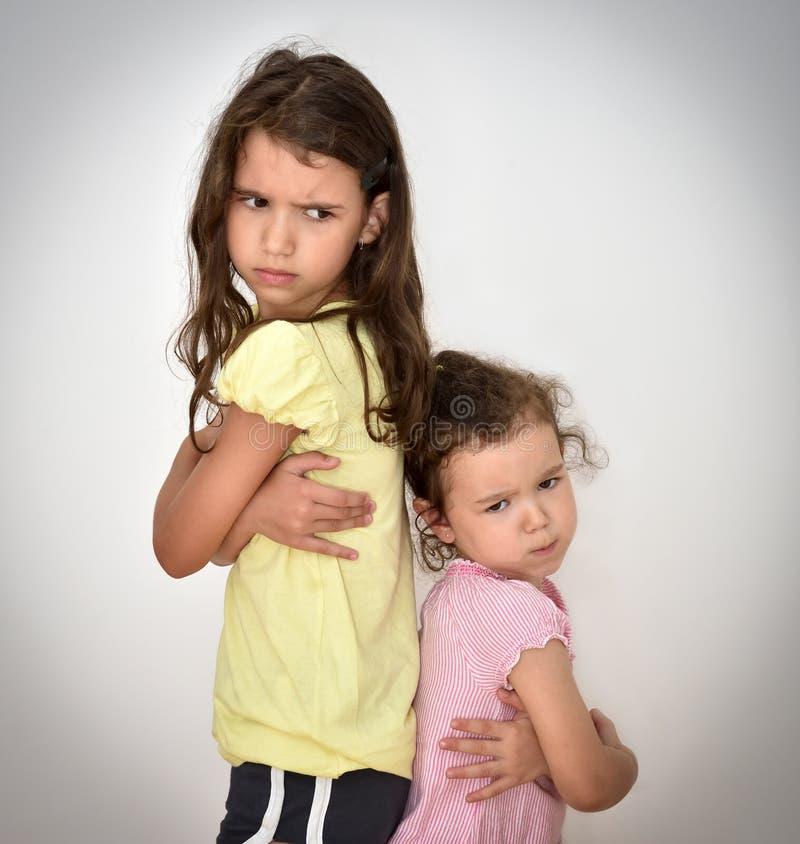 Zwei verärgerte Schwestern, die zurück zu Rückseite stehen lizenzfreies stockfoto