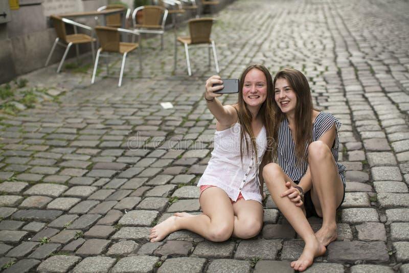Zwei vergnügte Jugendlichen tun selfie am Telefon, das auf der Pflasterung sitzt stockfoto