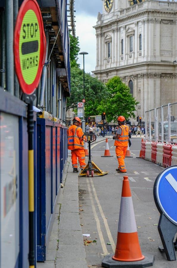 Zwei Verkehrsmarsch?lle gekleidet in den hallo-n?mlich orange Uniformen, die in einem veralteten Busfahrstreifen arbeiten stockfotografie
