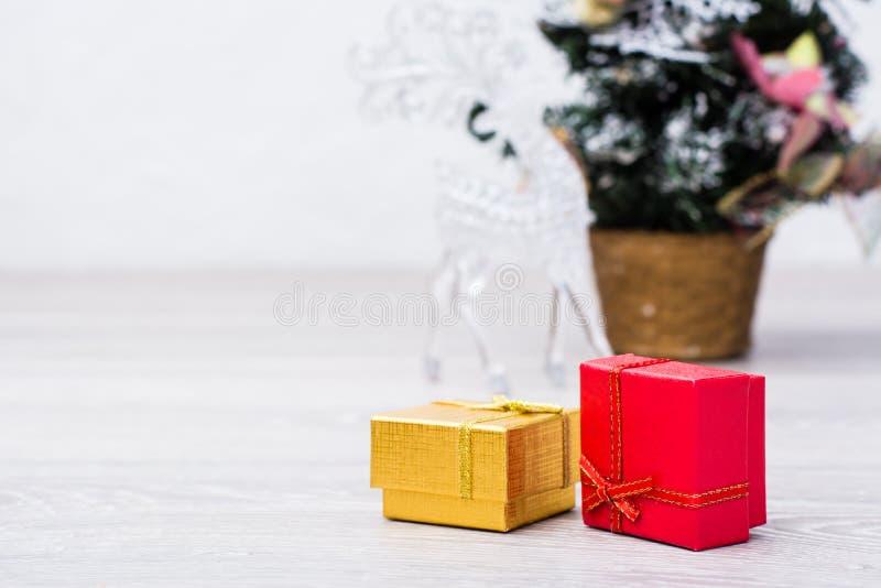 Zwei verpackte Geschenke in den Kästen und Weihnachtsdekorationen auf grauem hölzernem Hintergrund stockfotografie