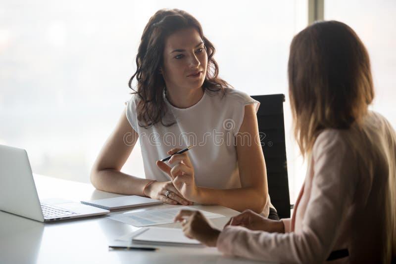 Zwei verschiedene ernste Geschäftsfrauen, die zusammenarbeiten im Büro sprechen stockfotografie