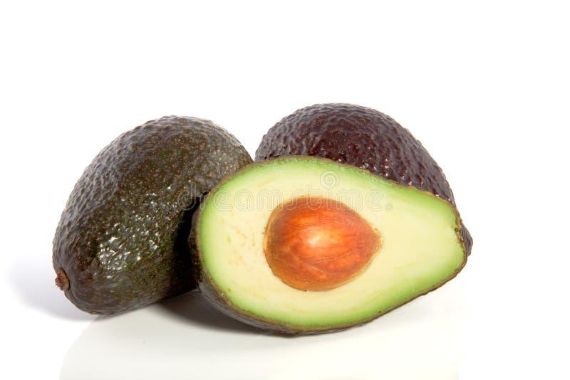 Zwei vollständig und Hälfe Avocado lizenzfreies stockfoto