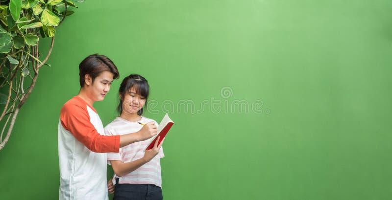 Zwei von den asiatischen Jugendstudenten, die zusammen herein an der grünen Wand studieren stockbilder