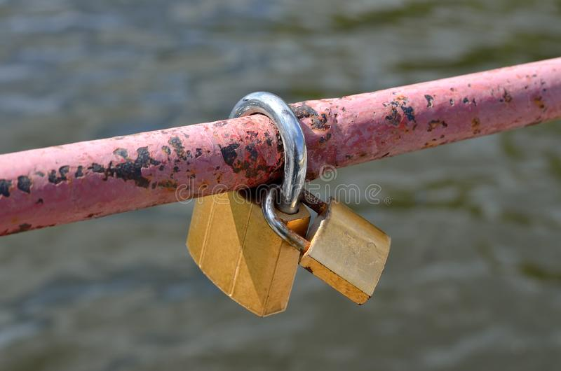 Zwei Vorhängeschlösser hängen an der Brücke als Symbol der Liebe lizenzfreies stockbild
