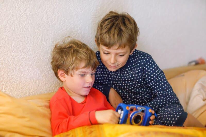 Zwei Vorschule- oder Schulkinderjungen, Geschwister und Brüder, die den nach der Schule Tag des Spaßes Videospiel zu Hause spiele lizenzfreie stockfotografie