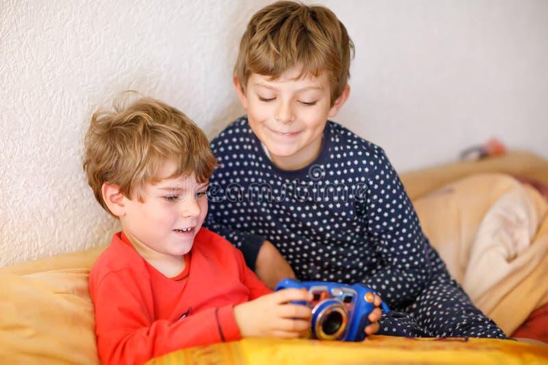 Zwei Vorschule- oder Schulkinderjungen, Geschwister und Brüder, die den nach der Schule Tag des Spaßes Videospiel zu Hause spiele stockfoto