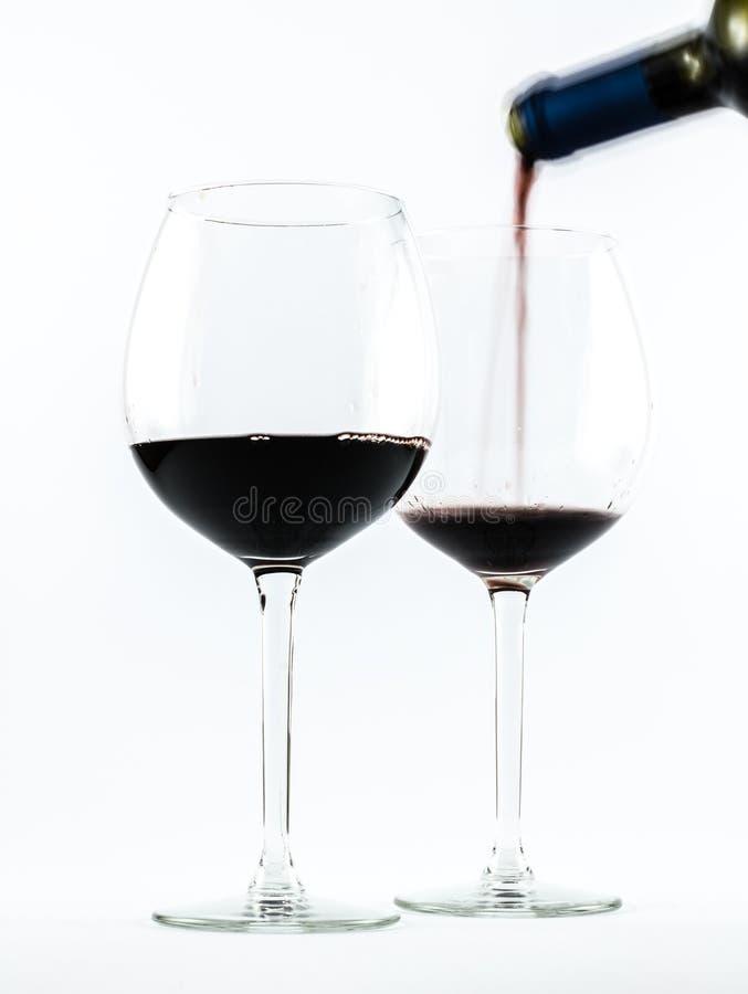 Zwei vorzügliche transparente Gläser mit Rotwein und einem strömenden Wein der Flasche auf einem weißen Hintergrund stockbild