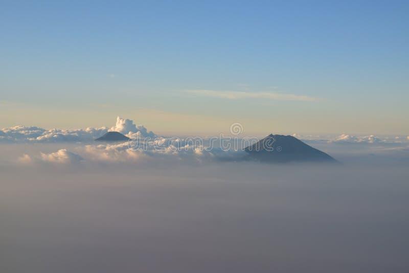 Zwei Vulkanberge sichtbar über der Wolke um Yogyakarta, Indonesien nahe Sonnenuntergang lizenzfreie stockbilder