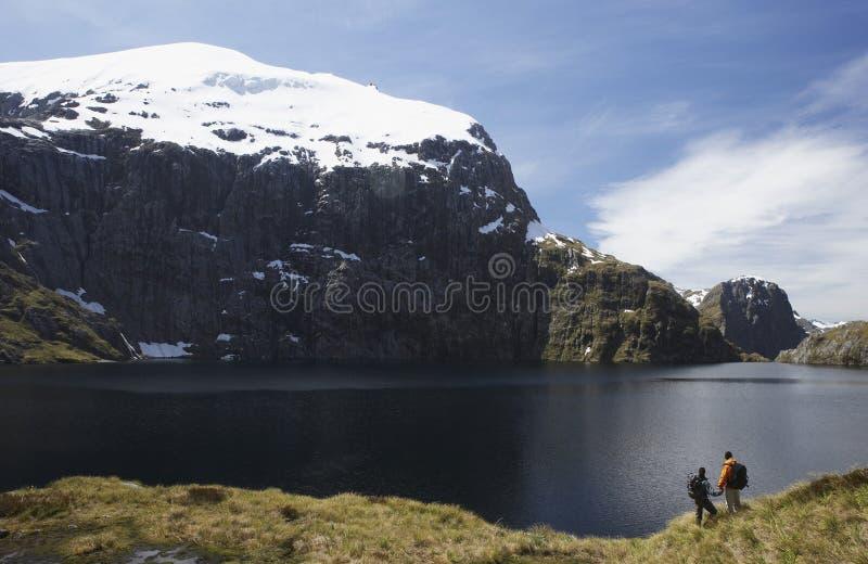 Zwei Wanderer, die Mountainsee betrachten lizenzfreie stockfotos