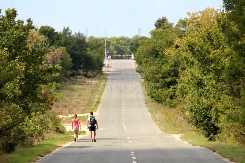 Zwei Wanderertouristen, die auf die lange gerade gepflasterte Straße geht ansteigend in Richtung zu geschlossenem Standort mit de lizenzfreie stockfotografie
