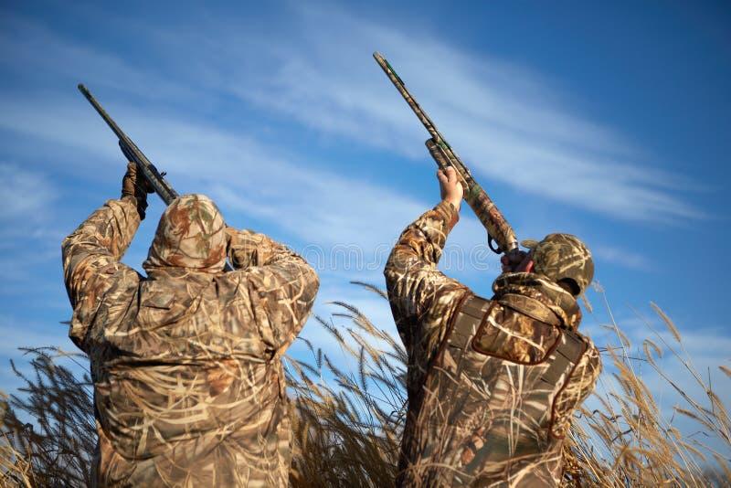 Zwei Wasservogeljäger, die in Himmel mit Gewehren zielen stockfotos