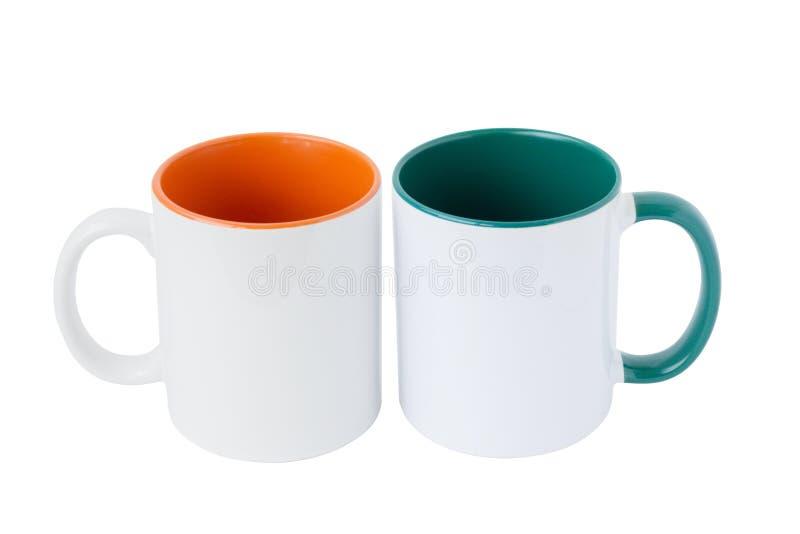 Zwei weiße Becher, mit einem grünen Griff lizenzfreie stockfotos