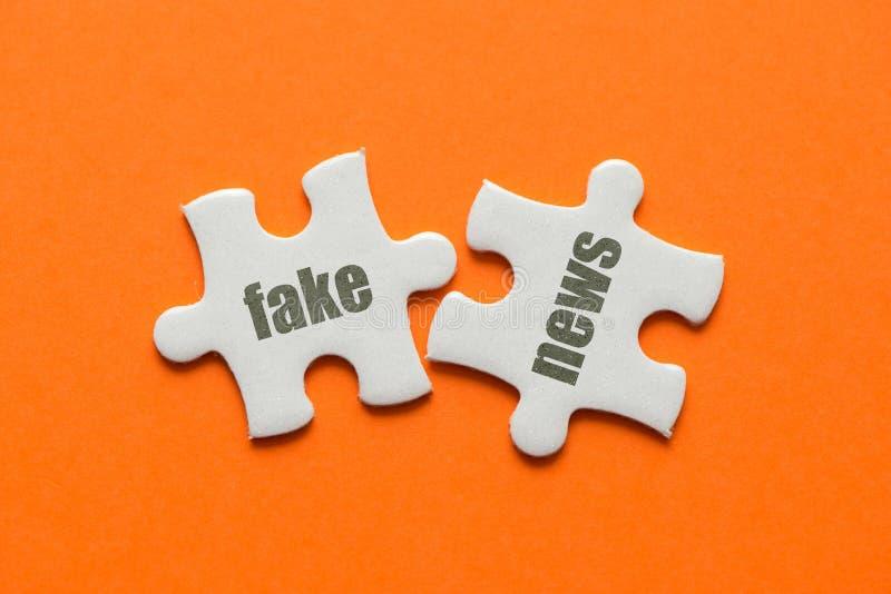 Zwei weiße Details Puzzlespiel mit Text fälschen Nachrichten auf orange Hintergrund, Abschluss oben lizenzfreie stockfotografie