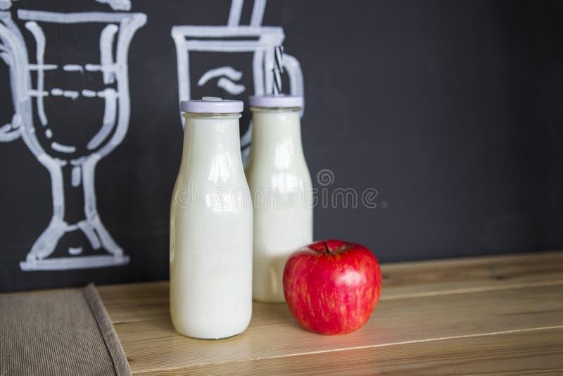 Zwei weiße Glasflaschen und ein frischer Apfel auf dem Tisch stockbilder