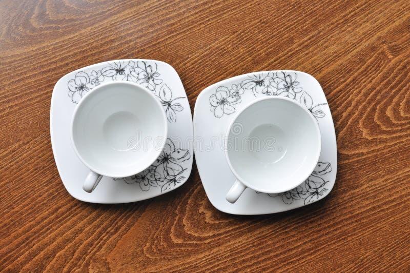 Zwei weiße Kaffeetassen auf Holztisch lizenzfreies stockbild