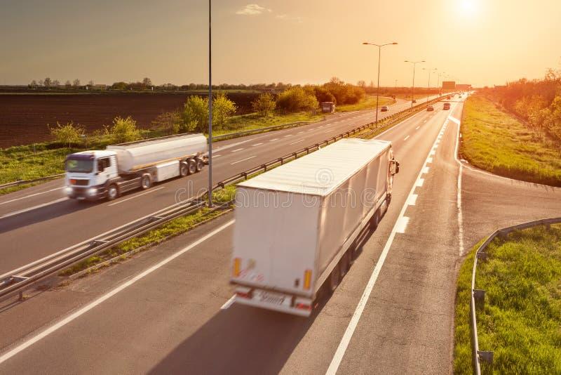 Zwei weiße LKWs auf der Autobahn bei Sonnenuntergang lizenzfreie stockbilder