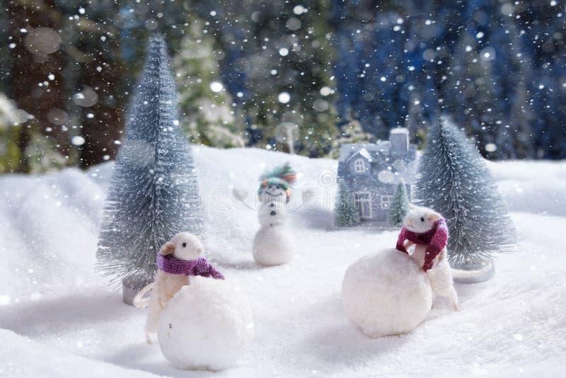 Zwei weiße Ratten rollen Schneebälle Im Hintergrund ein fröhlicher Schneemann und ein Haus lizenzfreies stockfoto