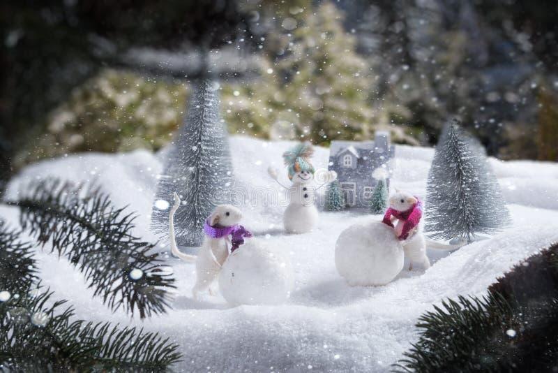 Zwei weiße Ratten rollen Schneebälle Im Hintergrund ein fröhlicher Schneemann und ein Haus stockbilder