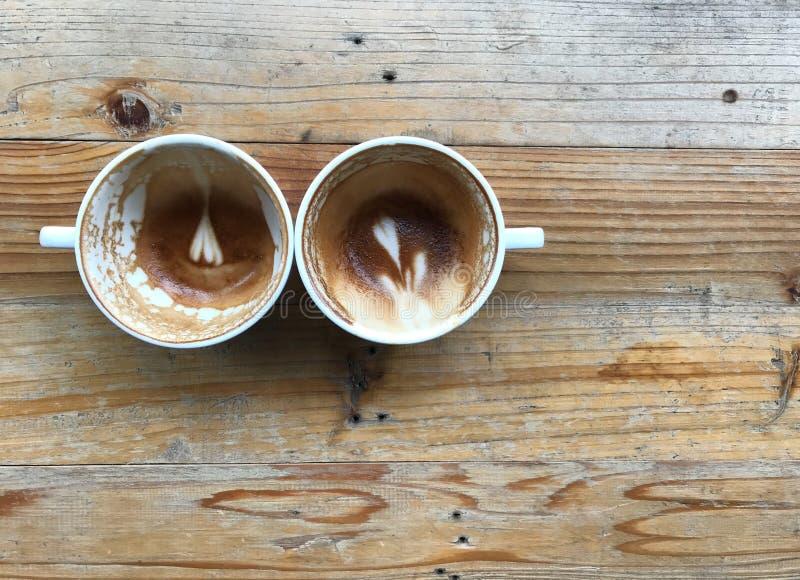 Zwei weiße Schalen fertiger Latte mit Blumen- und Herzform Lattekunst verließen in den Schalen auf hellbraunem Holztisch lizenzfreie stockfotos