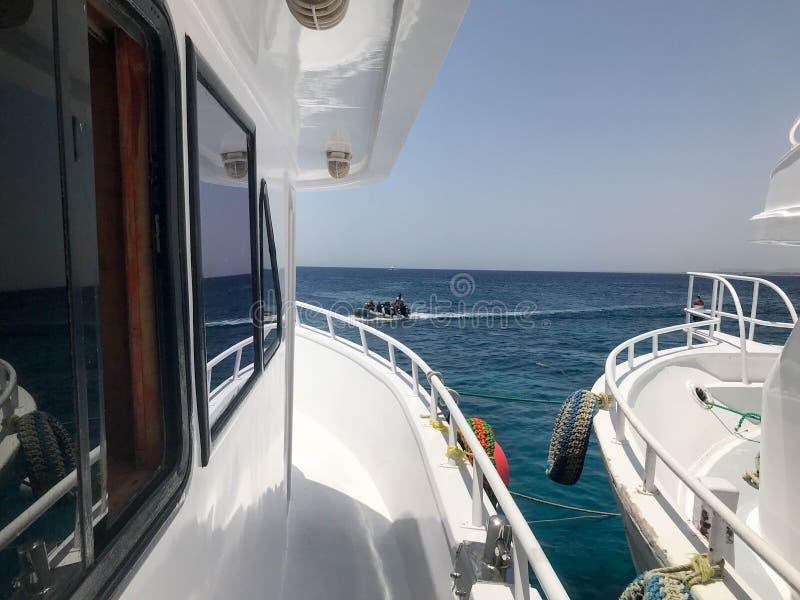 Zwei weiße Schiffe, ein Kreuzfahrtschiff, Yachten, Boote sehr, die nah, Brett zum Brett gegen das blaue Salzmeer, der Ozean in ei lizenzfreies stockbild