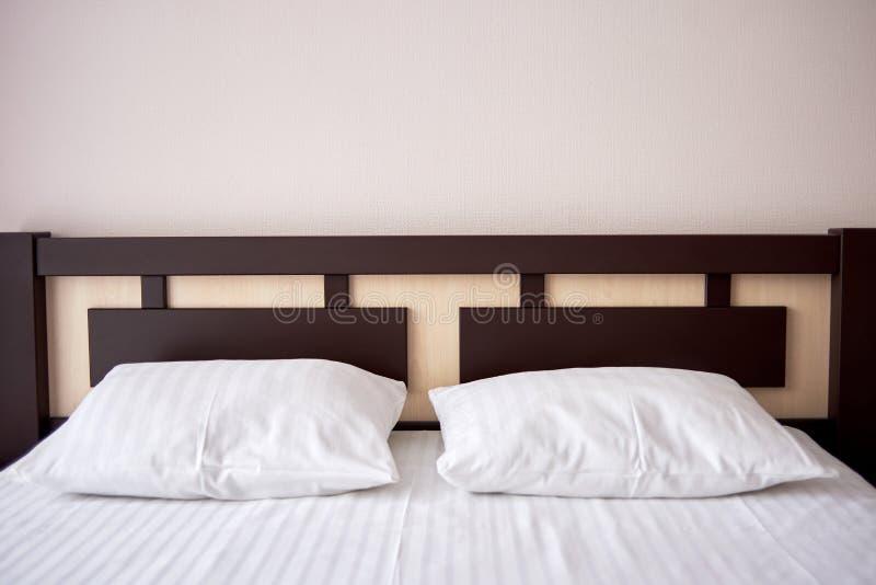 Zwei weiße weiche Kissen auf Bett mit brauner hölzerner Kopfende im Hotelschlafzimmerinnenraum, Kopienraum stockbilder