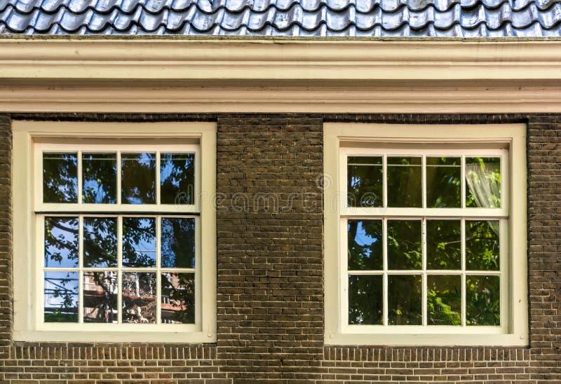 Zwei weiße Weinleseschiebefenster in der braunen Backsteinmauer lizenzfreies stockfoto