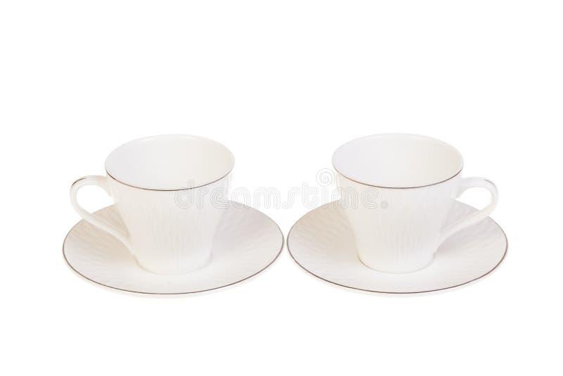 Zwei weißer Porzellantee, Kaffeetassen mit Untertasse Lokalisiert auf Weiß lizenzfreies stockbild