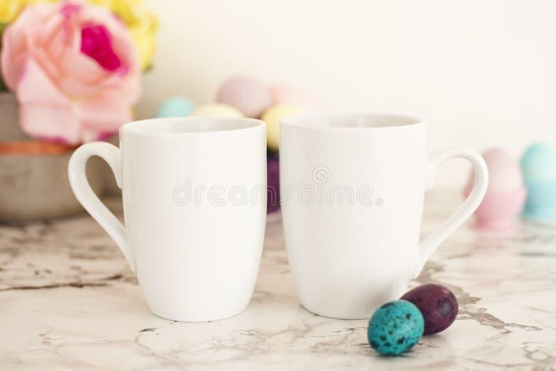 Zwei weißes Becher-Modell - Ostern-Thema Goldenes Ei über grünem Steigungshintergrund Bunte Eier in den Mattfarben Heller Marmorh stockfotos