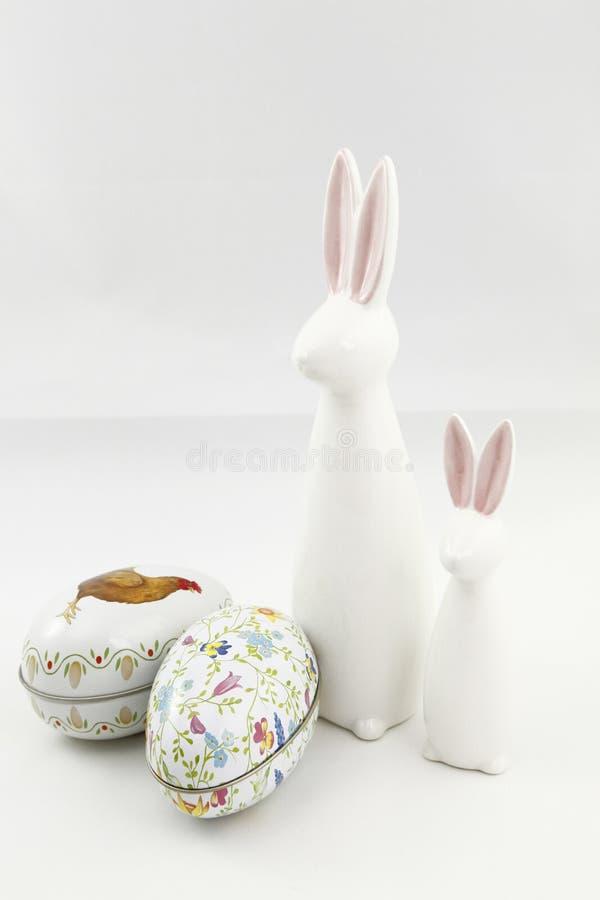Zwei weiße keramische Ostern-Kaninchen und zwei farbige Zinneier lizenzfreies stockbild